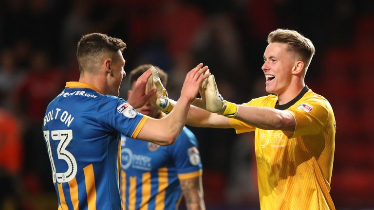 Shrewsbury Town's James Bolton celebrates with team-mate Dean Henderson after the final whistle