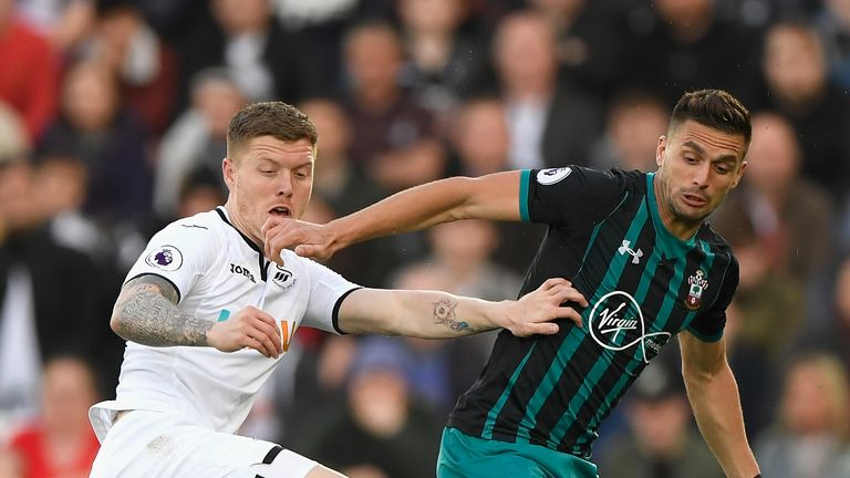Alfie Mawson battles for the ball with Dusan Tadic
