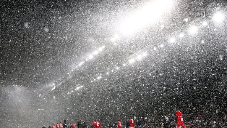 Manchester United and Brighton players walk out into heavy snow before the Emirates FA Cup, quarter final match at Old Trafford