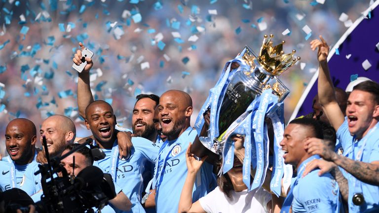 Vincent Kompany and his Manchester City teammates celebrate with the Premier League trophy as they're crowned champions at the Etihad Stadium