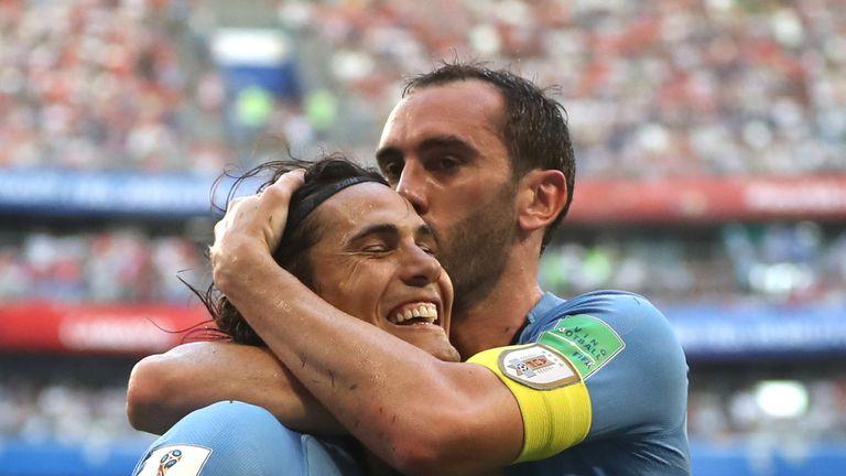 Edinson Cavani celebrates with team-mate Diego Godin after scoring Uruguay's third goal