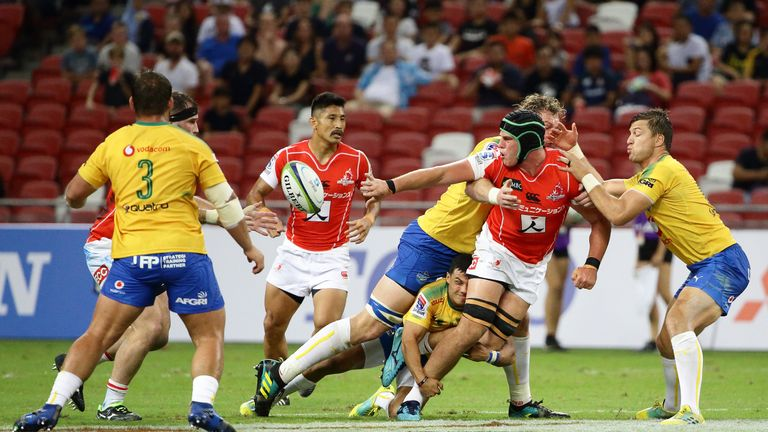 James Moore of the Sunwolves offloads as he is tackled by RG Snyman