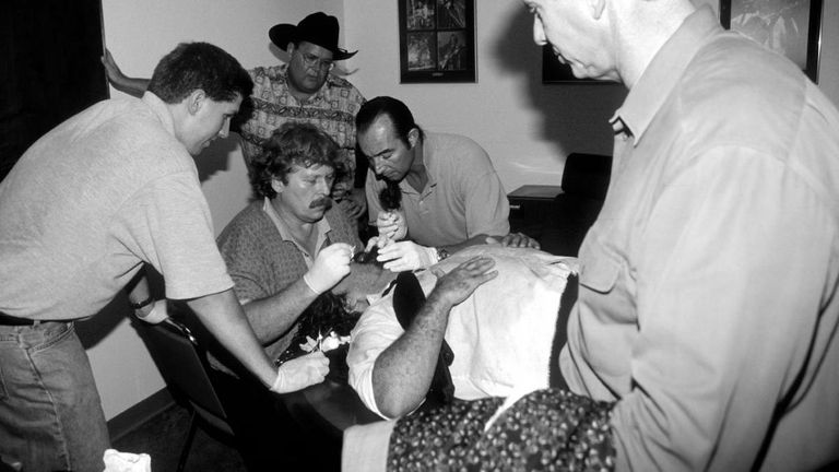 Jim Ross looks on as Foley is treated for his extensive injuries after the match