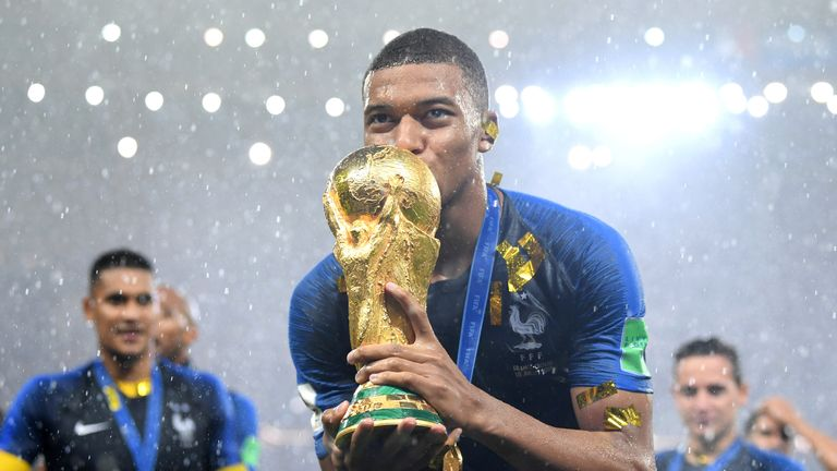 Kylian Mbappe celebrates with the World Cup trophy
