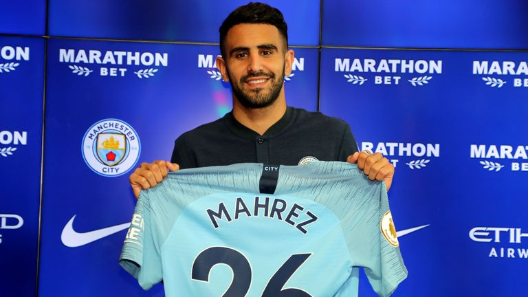 New Manchester City signing Riyad Mahrez holds up his shirt during the press conference at the City Football Academy