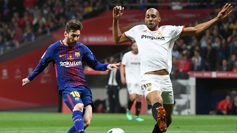Steven N'Zonzi of Sevilla attempts to dispossess Barcelona's Lionel Messi