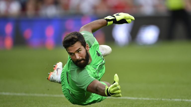 Alisson dives to his right