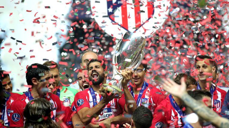 Diego Costa, del Atlético de Madrid, alza el trofeo tras ganar 4-2 la Supercopa de la UEFA al Real Madrid