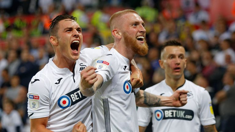 Oli McBurnie of Swansea City (C) celebrates his opening goal with team-mate Connor Roberts during the Sky Bet Championship match between Swansea City and Leeds United at the Liberty Stadium