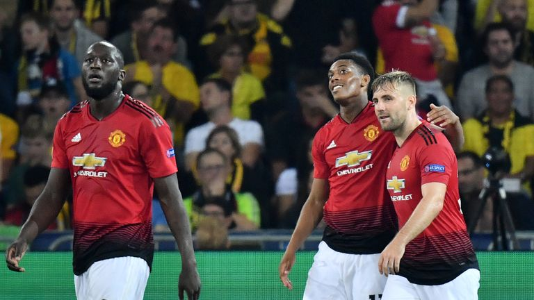 Manchester United's French striker Anthony Martial (C) celebrates after scoring with teammates Romelu Lukaku (L) and Luke Shaw (R) during the UEFA Champions League group H football match between Young Boys and Manchester United at The Stade de Suisse in Bern on September 19, 2018