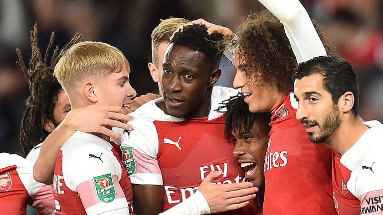 Arsenal's English striker Danny Welbeck (C) is mobbed by teammates after scoring the opening goal during the English League Cup third round football match between Arsenal and Brentford at the Emirates Stadium in London on September 26, 2018. (Photo by Glyn KIRK / AFP) / RESTRICTED TO EDITORIAL USE. No use with unauthorized audio, video, data, fixture lists, club/league logos or 'live' services. Online in-match use limited to 120 images. An additional 40 images may be used in extra time. No video emulation. Social media in-match use limited to 120 images. An additional 40 images may be used in extra time. No use in betting publications, games or single club/league/player publications. /         (Photo credit should read GLYN KIRK/AFP/Getty Images)