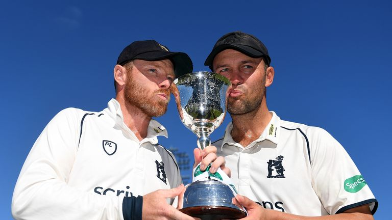 Ian Bell and Jonathan Trott of Warwickshire pose with the trophy after winning Division Two title