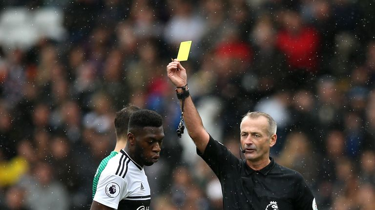 Timothy Fosu-Mensah is shown a yellow card by Martin Atkinson