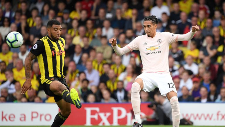 Troy Deeney of Watford (L) challenges for the ball with Chris Smalling of Manchester United during the Premier League match between Watford FC and Manchester United at Vicarage Road on September 15, 2018 in Watford, United Kingdom