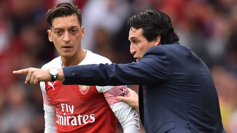 Arsenal's Spanish head coach Unai Emery gestures to Arsenal's German midfielder Mesut Ozil (L) on the touchline during the English Premier League football match between Arsenal and Manchester City at the Emirates Stadium in London on August 12, 2018
