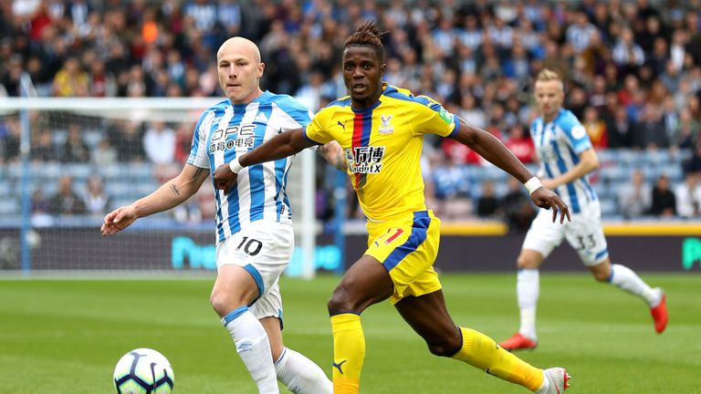 Wilfried Zaha battles for the ball with Aaron Mooy