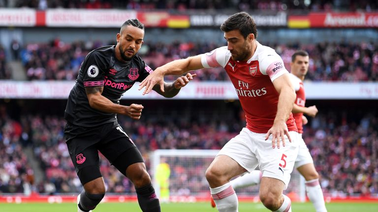 Sokratis and Theo Walcott battle for the ball