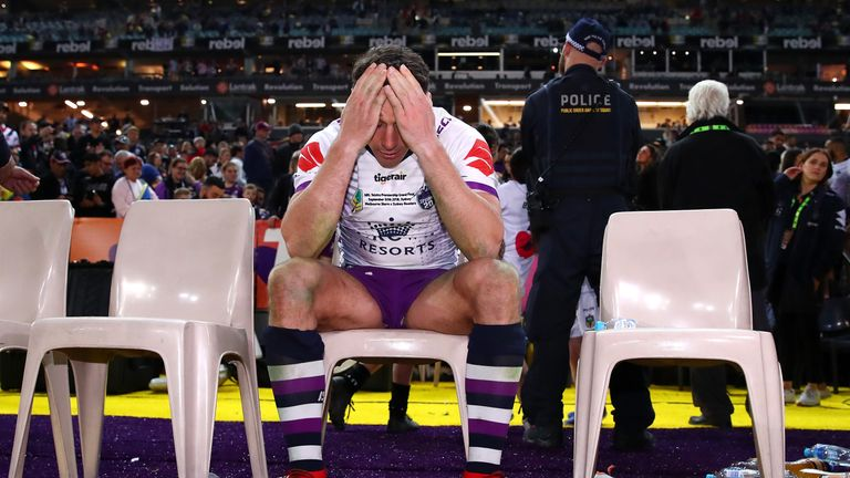 Billy Slater looks dejected as he sits down after playing his final NRL match
