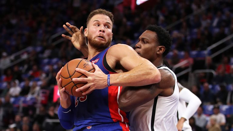 Blake Griffin of the Detroit Pistons tries to drive around Treveon Graham of the Brooklyn Nets