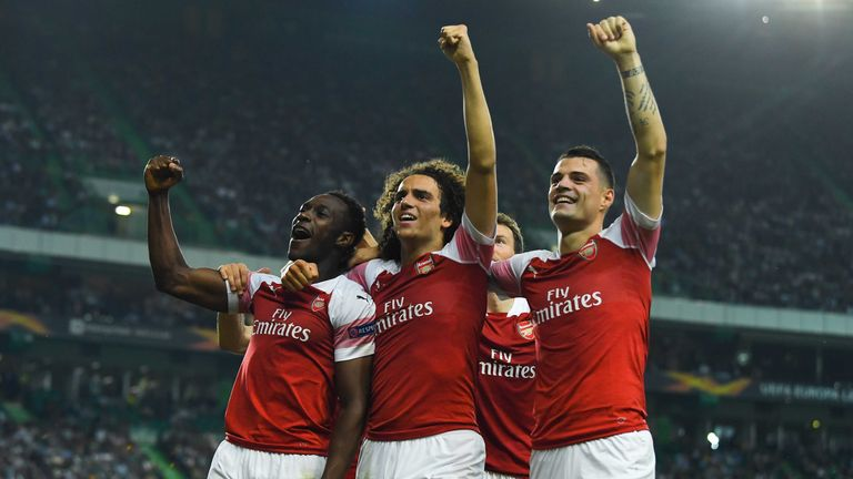 Arsenal players celebrate extending their winning run in all competitions with victory in Lisbon
