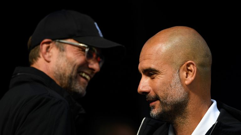 Jurgen Klopp, Manager of Liverpool smiles as Josep Guardiola, Manager of Manchester City looks on prior to the Premier League match between Manchester City and Liverpool at Etihad Stadium on September 9, 2017