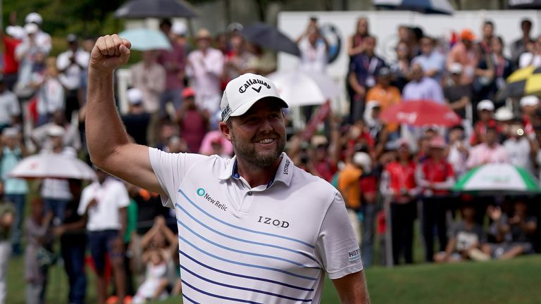 Leishman pumps his fist in celebration on the 18th green after a closing birdie