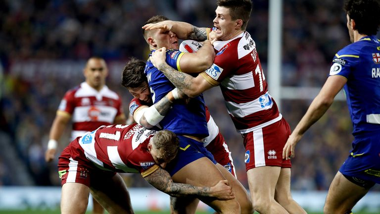 Warrington Wolves' Tom Lineham (centre right) is tackled by Wigan Warriors' John Bateman