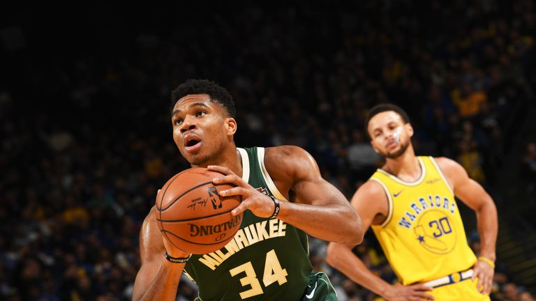 Giannis Antetokounmpo shoots a free throw as a frustrated Stephen Curry looks on