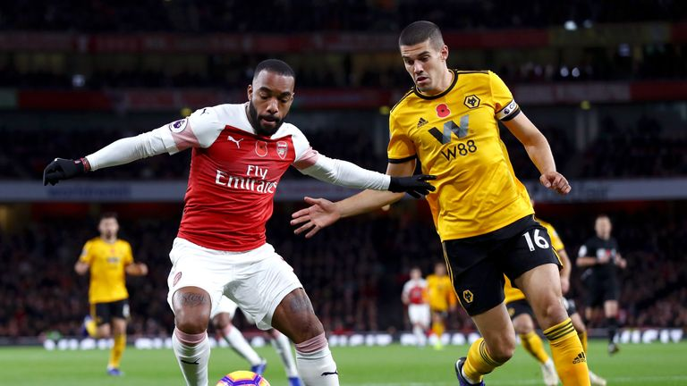 Alexandre Lacazette battles for possession with Conor Coady