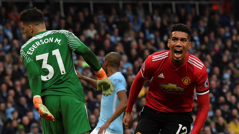 Manchester United's English defender Chris Smalling (R) celebrates scoring their third goal during the English Premier League football match between Manchester City and Manchester United at the Etihad Stadium in Manchester, north west England, on April 7, 2018.