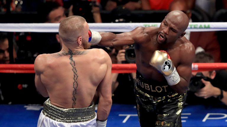 (L-R) Floyd Mayweather Jr. throws a punch at Conor McGregor during their super welterweight boxing match on August 26, 2017 at T-Mobile Arena in Las Vegas, Nevada.