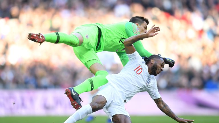 Croatia goalkeeper Lovre Kalinic collides with Raheem Sterling