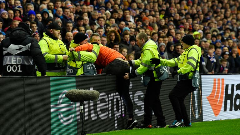 A man is led away by stewards during Rangers' game against Villarreal