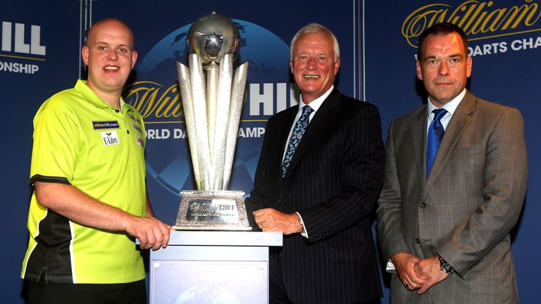 Chief Marketing Officer at William Hill Kristof Fahy (R) and Michael van Gerwen of Holland (L) and PDC Chairman Barry Hearn (C) pose for a photo with the Sid Waddell trophy during William Hill World Darts Championship Sponsorship Launch at Rileys Sports Bar on June 13, 2014 in London, England.