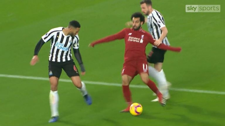 Liverpool forward Mo Salah (centre) goes over under a challenge from Newcastle defender Paul Dummett