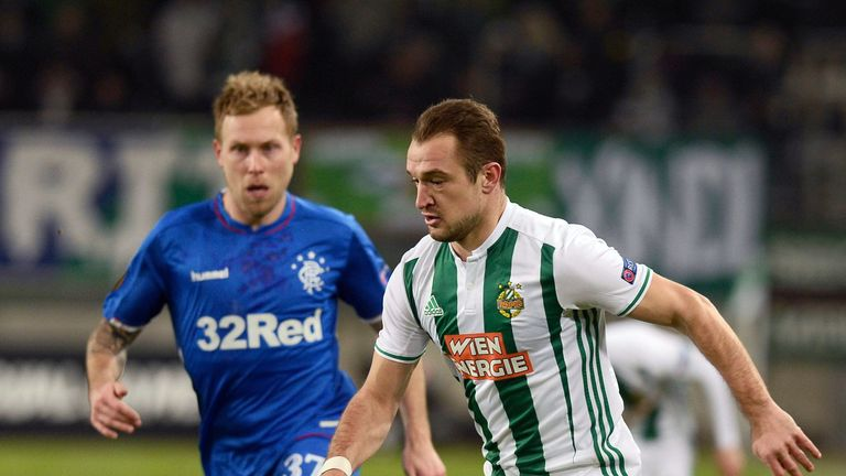 Rapid Wien's Norwegian forward Veton Berisha and Glasgow Rangers' Canadian midfielder Scott Arfield (L) vie for the ball during the UEFA Europa League Group G football match between Rapid Wien and Glasgow Rangers on December 13, 2018 in Vienna.