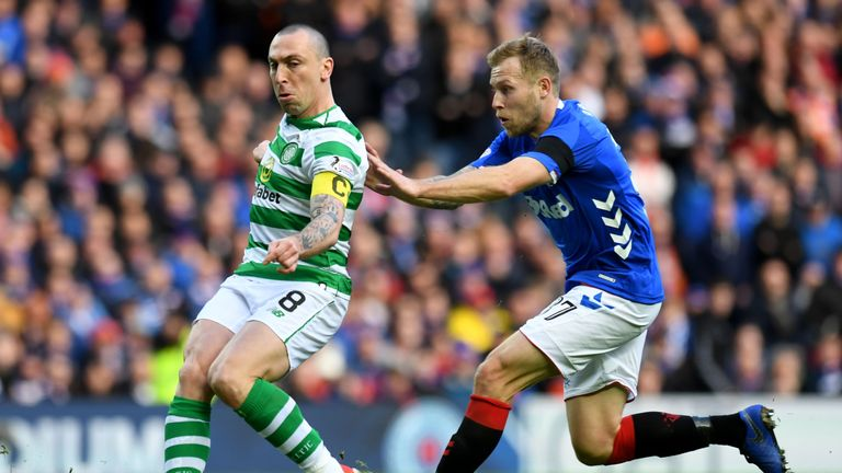 Celtic captain Scott Brown clears the ball from Rangers Scott Arfield