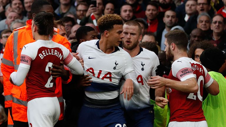 Tottenham Hotspur's English midfielder Dele Alli (C) is restrained after celebrating Dier's equalizer during the English Premier League football match between Arsenal and Tottenham Hotspur at the Emirates Stadium in London on December 2, 2018.
