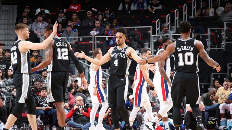 Derrick White high-fives his Spurs team-mates