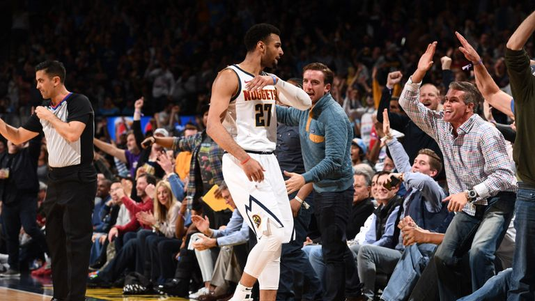 Jamal Murray high-fives with Nuggets fans after hitting a half-court shot