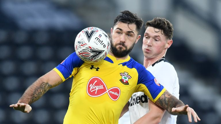 Southampton striker Charlie Austin shields the ball from George Evans