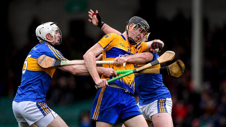 Family ties: Brothers Ronan and Padraic Maher of Tipperary hold up Colin Guilfoyle of Clare