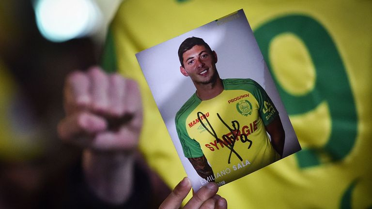 A member of the public holds up a photograph of missing footballer Emiliano Sala during a vigil in Nantes, western France