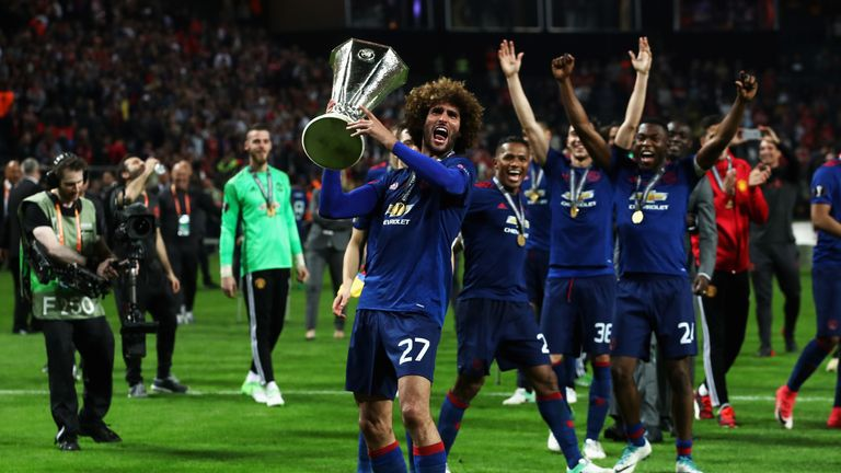 Marouane Fellaini holds up the Europa League trophy