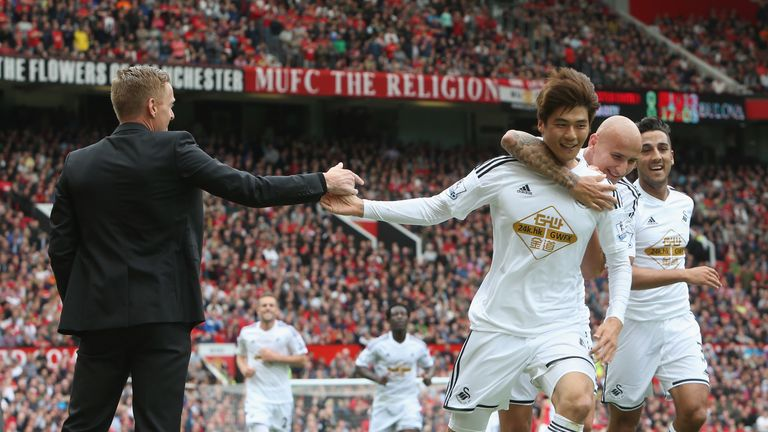 Swansea's Ki Sung-Yueng celebrates with Garry Monk against Manchester United at Old Trafford on August 16, 2014 in Manchester, England.