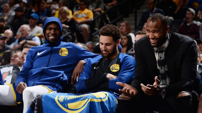 Kevin Durant #35, Klay Thompson #11, and DeMarcus Cousins #0 of the Golden State Warriors react to a play during the game against the Denver Nuggets on October 21, 2018 at the Pepsi Center in Denver, Colorado.