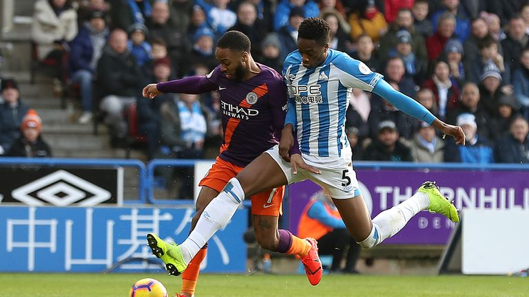 Manchester City's Raheem Sterling (left) and Huddersfield Town's Terence Kongolo battle for the ball