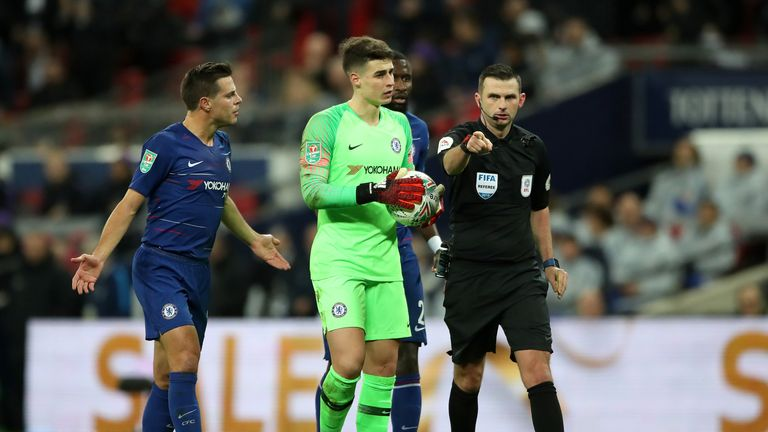 Match referee Michael Oliver points to the penalty spot after a foul by Chelsea goalkeeper Kepa Arrizabalaga during the Carabao Cup, semi final match at Wembley, London
