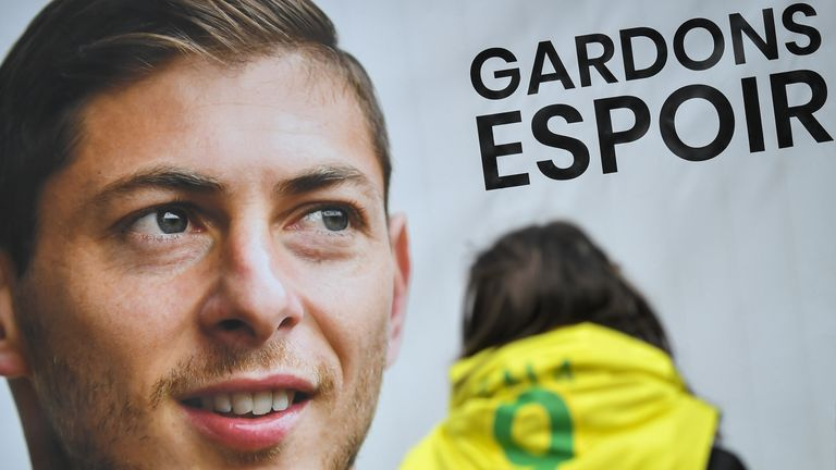 An FC Nantes supporter stands beside a portrait of Emiliano Sala outside the club's training centre