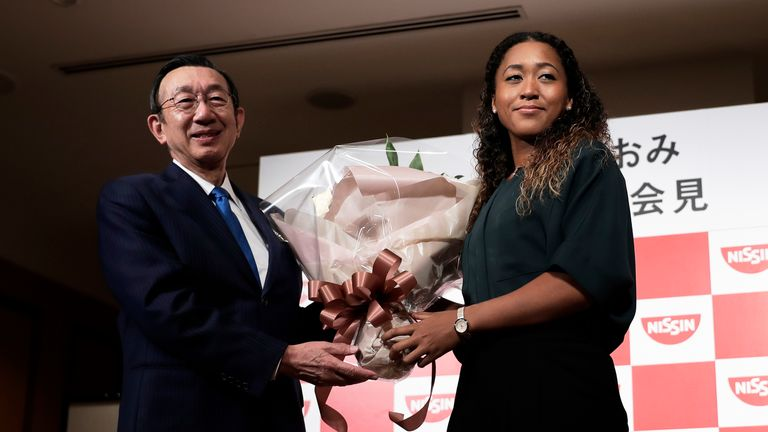Osaka receives a bouquet from Koki Ando, president of Nissin, after winning the US Open